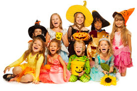 stock photo of halloween  - Happy big group of children in Halloween costumes sitting together isolated on white with pumpkin and sunflower and bucket for candies - JPG