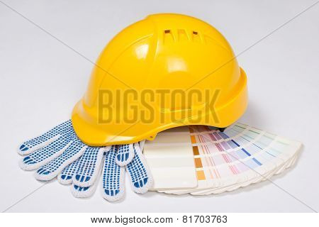 Builder's Yellow Helmet, Work Gloves And Colorful Palette Over White