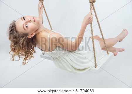 beautiful young blond woman on a swing.