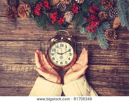 Female Holding Alarm Clock On A Table.