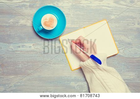 Female Hand Writing In Notebook Near Cup Of Coffee.