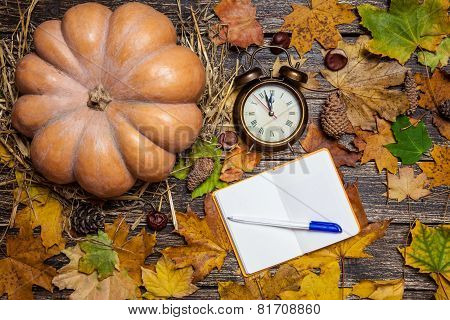 Alarm Clock And Note With Pen On Autumn Table.