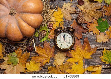 Alarm Clock On Autumn Table.