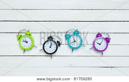 Four Alarm Clocks On White Background.