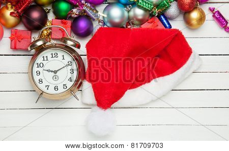 Alarm Clock And Santa's Hat With Christmas Gifts.