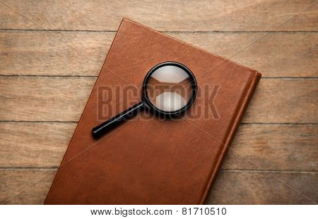 Closed Book And Loupe On It.