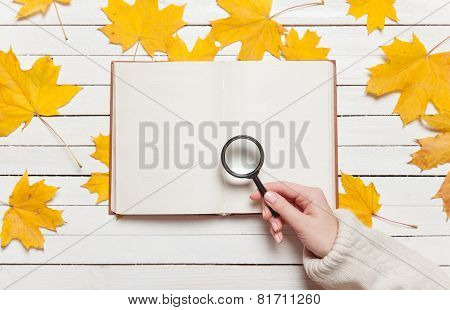 Female Hand Holding Loupe Over Book