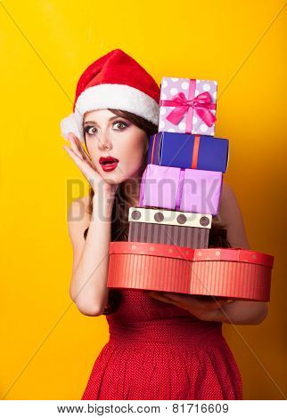 Beautiful Brunette Girl In Christmas Hat With Gift On Yellow Background.