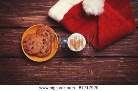 Cookie And Cup Of Coffee With Santa's Hat On Wooden Table.