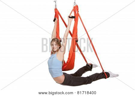 Young woman doing anti-gravity aerial yoga in  red hammock on a seamless white background.