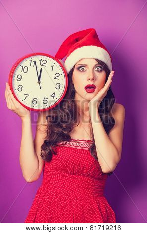 Beautiful Brunette Girl In Christmas Hat With Huge Clock On Violet Background.