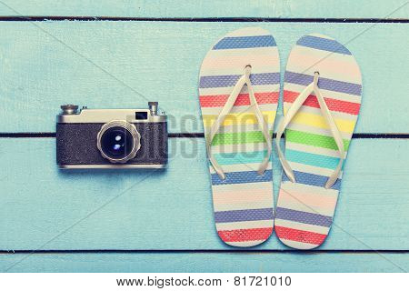 Camera And Slippers On Wood