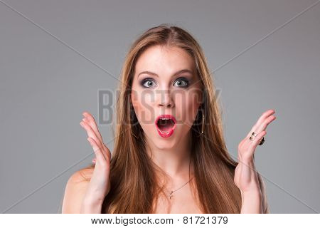 Close-up portrait of surprised beautiful girl holding her head in amazement and open-mouthed.