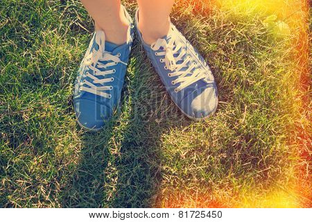 Blue Sneakers On Saturated Green Grass. Photo In Old Color Image Style.