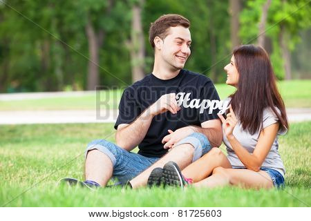 Teen Couple With Word Happy In The Park.