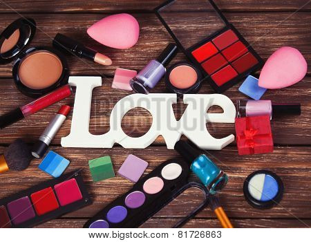 Cosmetics And Word Love On Wooden Table