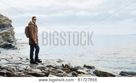 Traveler Hipster Man Standing On Coastline Near The Sea