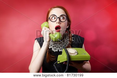 Redhead Girl With Green Phone On Red Background.
