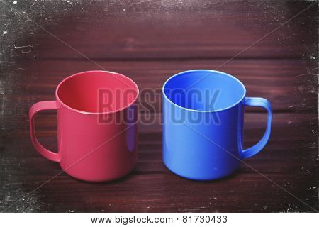 Two Color Cups On Woodent Table.