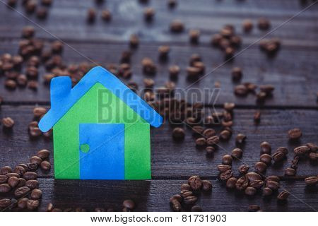 Paper House And Coffee Beans On Wooden Table.
