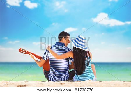 Young Couple With Guitar On The Beach In Summer Day