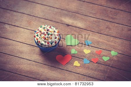 Cupcake And Paper Hearts On Wooden Background.