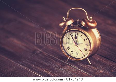 Retro Alarm Clock On A Table. Photo In Retro Color Image Style