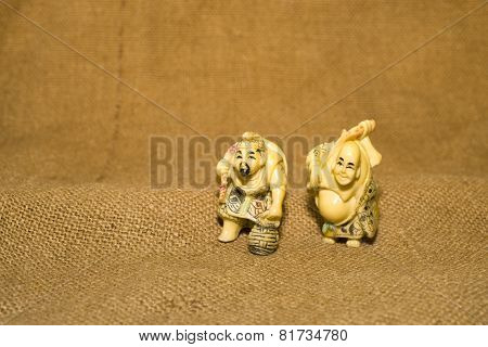 Two Figures Of Chinese Men On The Background Of Old Cloth