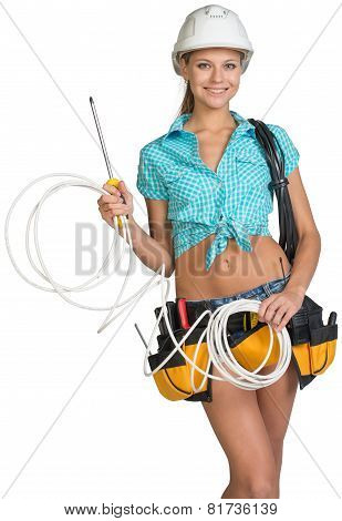 Woman in hard hat and tool belt holding coil of cable