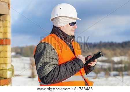 Engineer with tablet PC near building