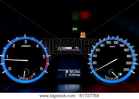 Backlit Gauges Of An Automobile. Blue Glowing Meters With A White Needle. Fuel, Tachometer, And Spee