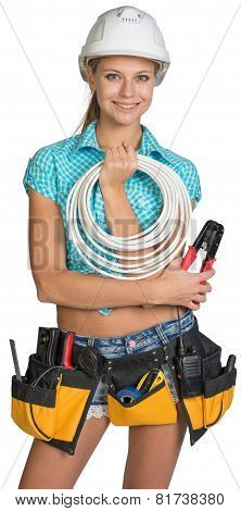 Pretty electrician in helmet, shorts, shirt, tool belt with tools holding an electric cable