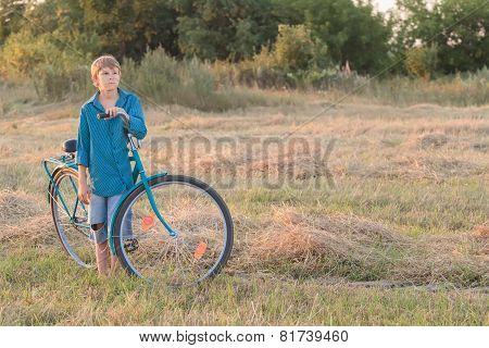 Teenager Boy With Blue Bike In Farm Field