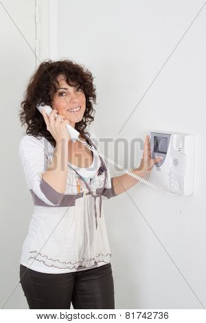 Woman Inside A Home Answering Security Phone
