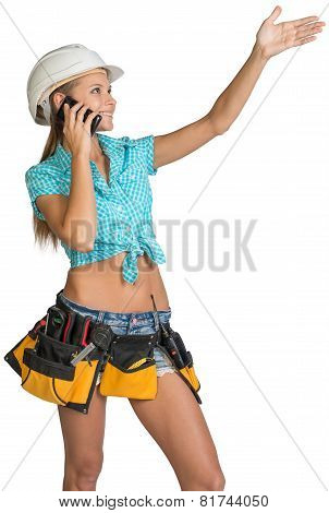 Woman in hard hat calling on mobile phone and showing direction