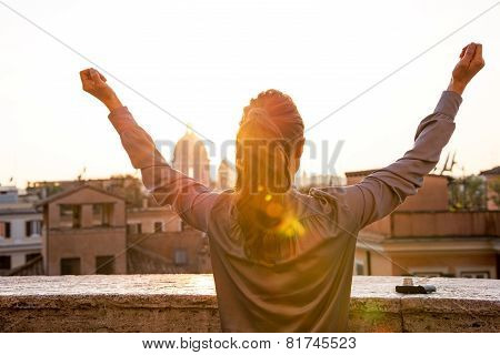 Young Woman Looking On Rome Panorama On Sunset And Rejoicing. Rear View