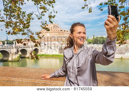 Smiling Young Woman Making Selfie On Embankment Near Castel Sant'angelo In Rome Italy