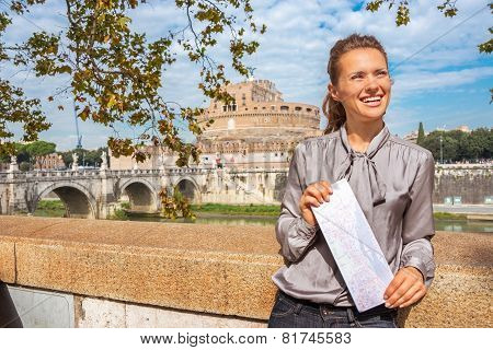 Portrait Of Smiling Young Woman With Map On Embankment Near Cast