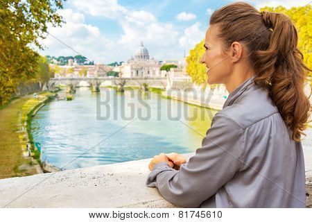 Young Woman Looking Into Distance While On Bridge With View On B