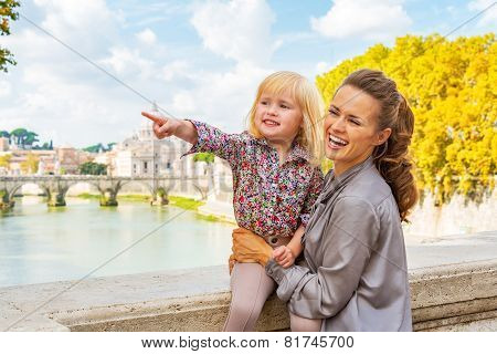 Happy Mother And Baby Girl Pointing While On Bridge Ponte Umberto I With View On Basilica Di San Pie