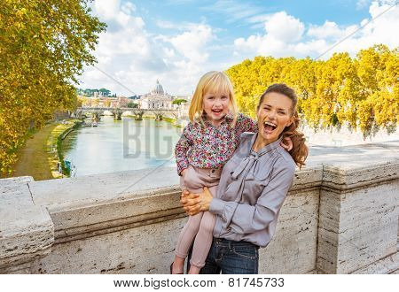 Portrait Of Happy Mother And Baby Girl On Bridge Ponte Umberto I With View On Basilica Di San Pietro