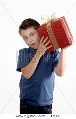 Child shaking a wrapped present