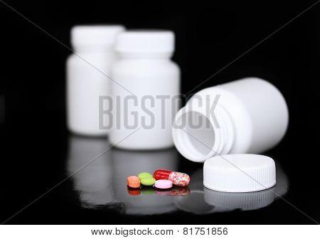 White Medicine Bottle, Color Pills On Black .