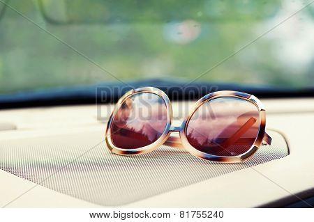 Elegant Fashionable Plastic Women's Sunglasses On Interior Car Dashboard.