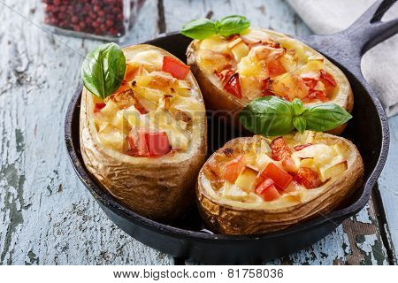 Stuffed potatoes with cheese and tomatoes in a pan