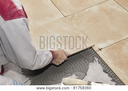 Home improvement, renovation - construction worker tiler is tiling ceramic tile floor.