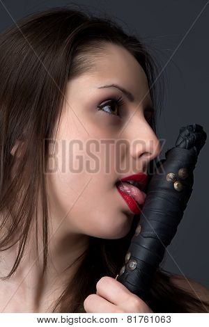 Image of the brunette licking a whip