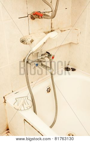 Old dirty tap on the bath
