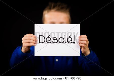 Child Holding Sign With French Word Desole - Sorry