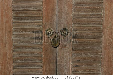 Padlock and weathered wooden doors